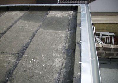 Fläche + Rand - und Wandanschlüsse mit einer Dampfsperrbitumenbahn eingedichtet. Vorgehängte Rinne + Traufblech montiert.